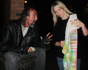 Christy blesses a homeless man, by buying a shirt from him that he made.